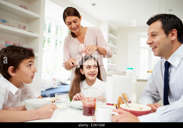Family Having Breakfast Before Husband Goes To Work - Stock Image