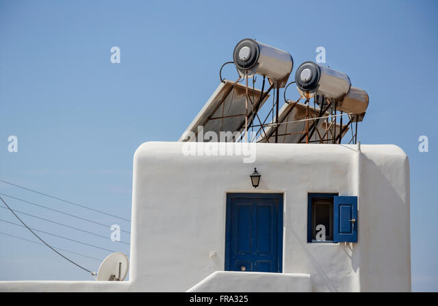 Modern solar panel powered hot water heaters for energy efficiency are mounted on the roof of a traditional greek - Stock Image