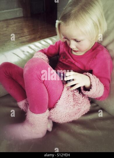 A girl curled on a couch plays with her tablet. - Stock Image