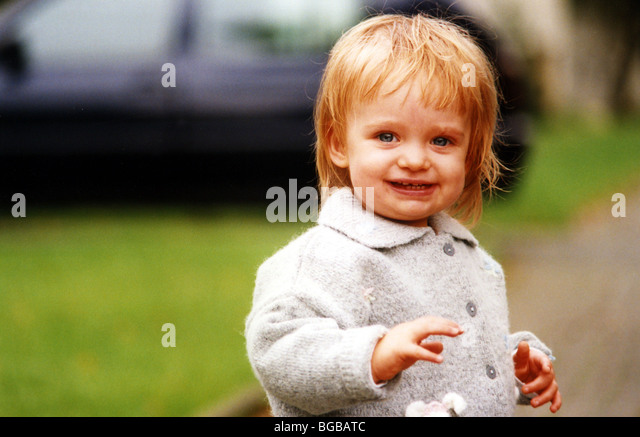 Photograph of young girl outside smile happy walking toddler UK - Stock-Bilder