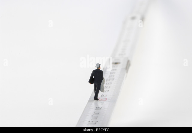 Business man figurine walking on measuring tape - Stock Image