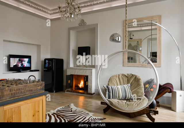 Eero Aarnio bubble chair in living room with zebra skin rug and fireplace - Stock Image