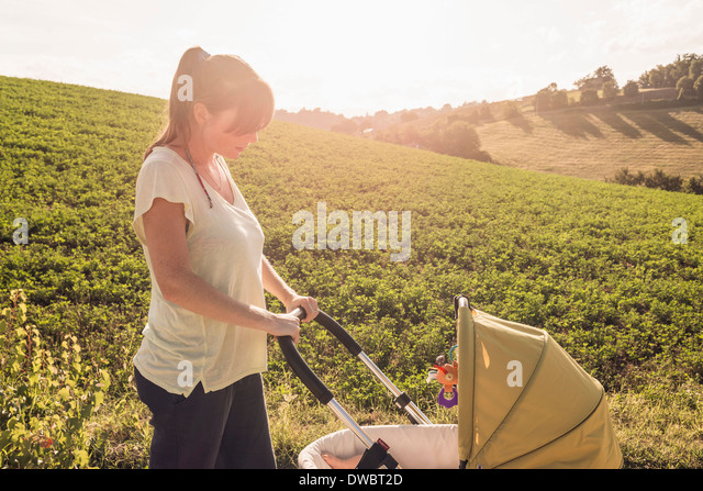 Mother strolling in countryside pushing baby pram - Stock Image
