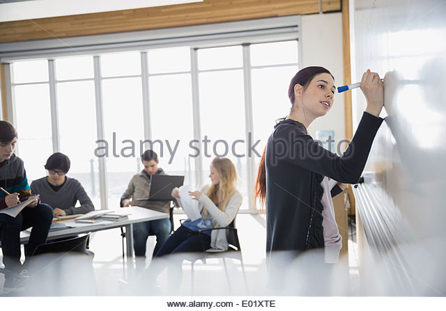 High school student at whiteboard in classroom - Stock Image