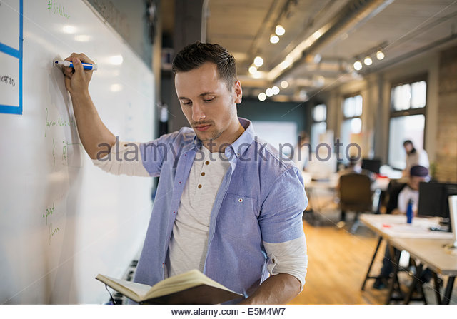 Businessman with book writing on whiteboard in office - Stock-Bilder