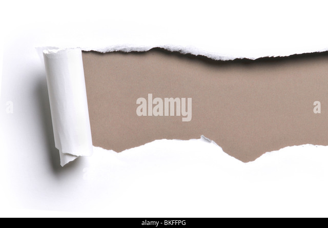 ripped white paper against a brown background - Stock Image