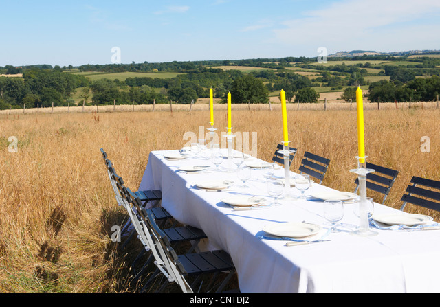 Table settings in wheatfield - Stock Image
