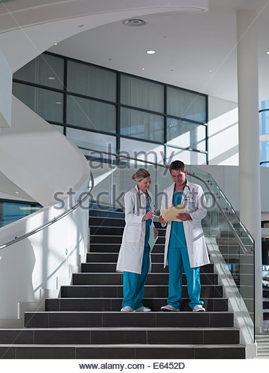 Doctors walking down staircase in hospital - Stock-Bilder