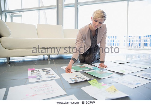 Creative businesswoman reviewing proofs in office - Stock Image