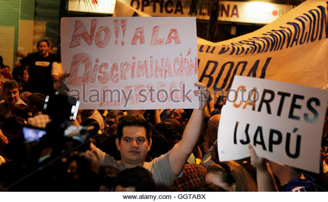 A man with a sign that says 'No to labor discrimination' during a protest march by civil servants dismissed - Stock Image