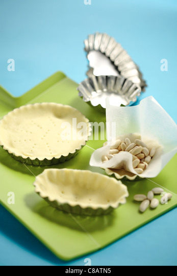 Placing the pastry in the moulds - Stock Image