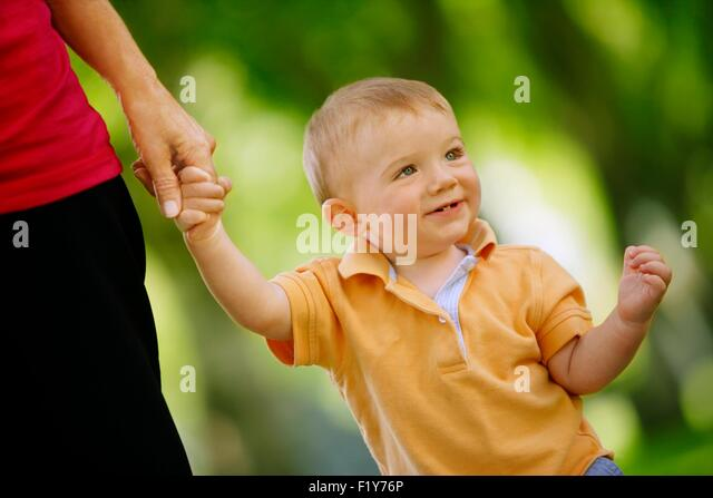 Toddler Walking While Holding Adult's Hand - Stock Image