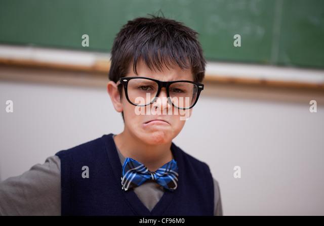 Grumpy schoolboy posing - Stock Image