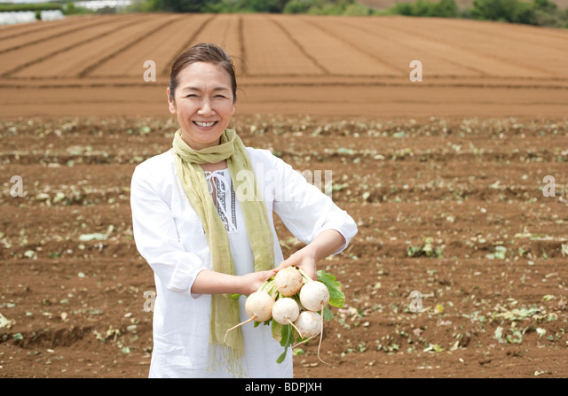 Mature woman holding turnip on field - Stock Image