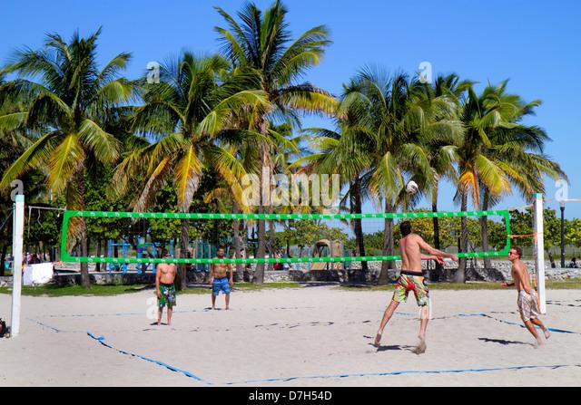 Miami Beach Florida Lummus Park volleyball game net sand man playing 2 on 2 - Stock Image