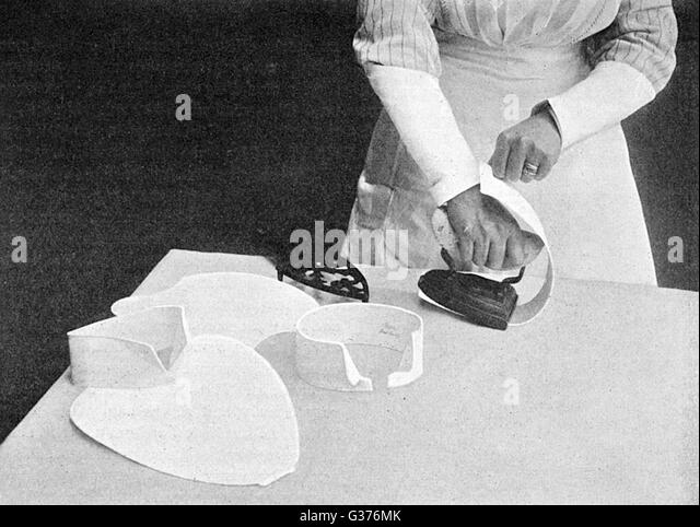 Photograph demonstrating the  technique for ironing bib and  collars in 1911.        Date: 1911 - Stock Image