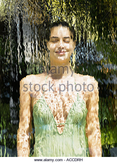 Woman in a bathing suit behind a waterfall - Stock Image