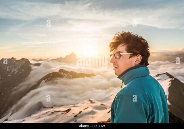 Young male mountain trekker looking at view above clouds, Bavarian Alps, Oberstdorf, Bavaria, Germany - Stock-Bilder