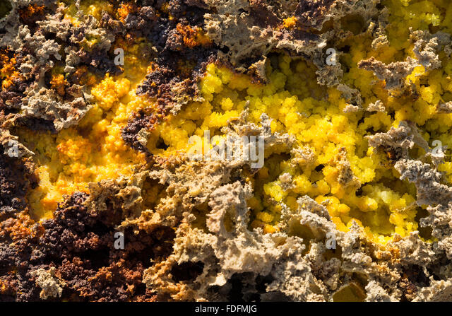 Tiny crystals of sulphur and salt lie in the cracks in the crust near Dallol, Ethiopia - Stock Image