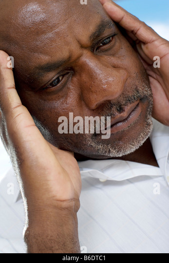 Depression. Unhappy man resting his head on his hand. - Stock Image