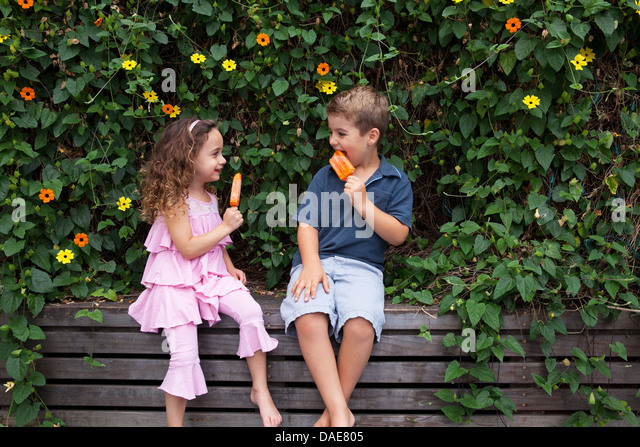Brother and sister eating ice lollies by plants - Stock-Bilder