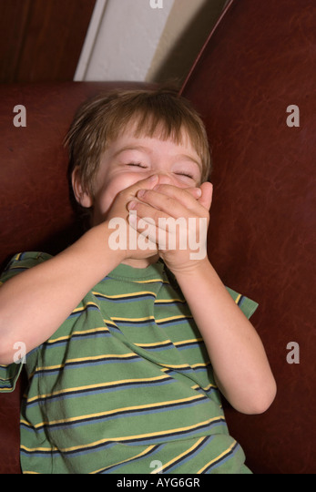 five year old boy covering mouth with both hands, trying not to laugh - Stock Image