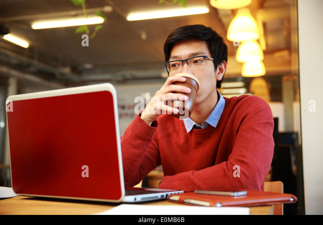 Handsome asian man working on laptop and drinking coffee - Stock Image