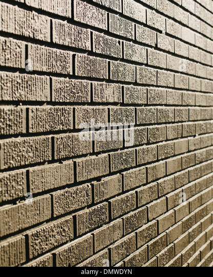 A brown brick wall in a city. - Stock Image
