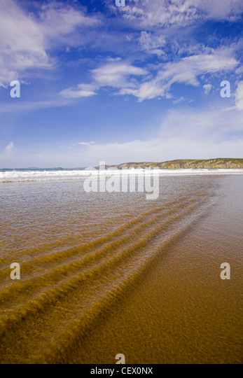 Ripples in the shallow surf at Newgale beach. - Stock Image