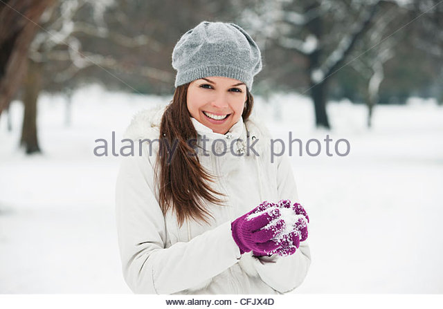 A young woman wearing a grey woolen beret, holding a snowball - Stock Image