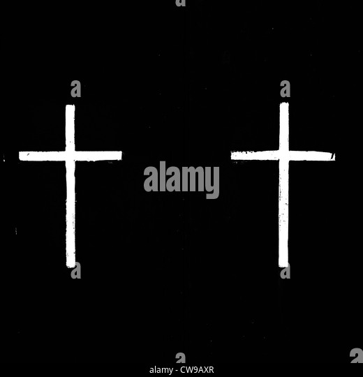 two white, painted crosses on a black background - Stock Image