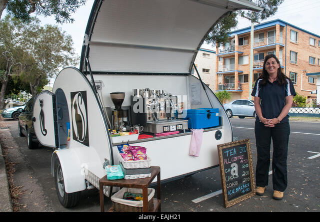 Female entrepreneur operating a roadside mobile coffee bar beside a beach at Caloundra, Sunshine Coast, Queensland, - Stock-Bilder
