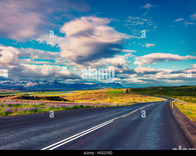 Empty asphalt road with colorful cloudy sky. Beautiful outdoor scenery in Iceland, Europe. - Stock Image
