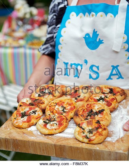 Woman holding mini-pizzas on wooden board - Stock Image