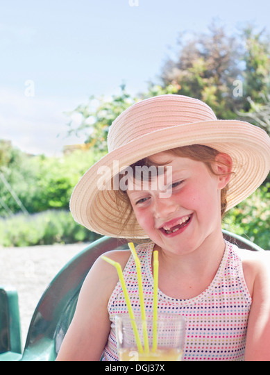 Girl wearing sunhat with soft drink - Stock Image