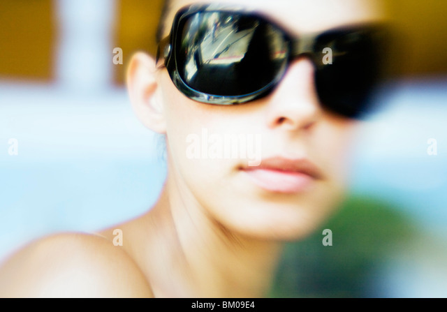 Close up of a young woman wearing sunglasses in the summer - Stock Image