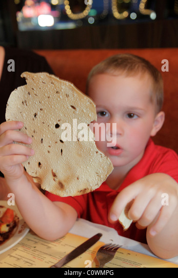 Florida Kissimmee Passage to India Restaurant papadum cracker flatbread boy holding - Stock Image