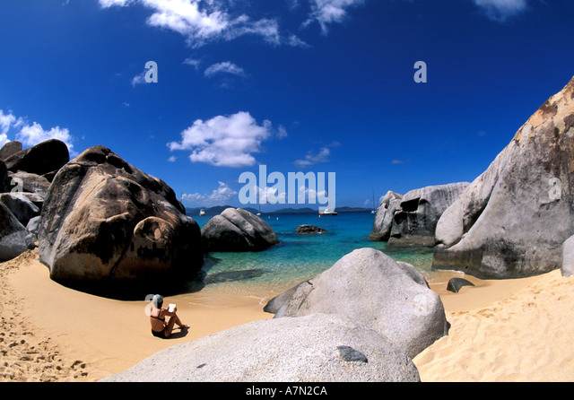 British Virgin Islands Virgin Gorda woman reading book on the beach at The Baths National Park - Stock Image