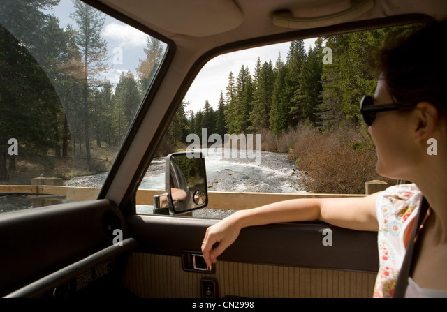 Woman looking through car window at forest scenery - Stock Image