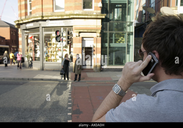 Manchester England UK Deansgate man mobile cell phone pedestrian street crossing - Stock Image