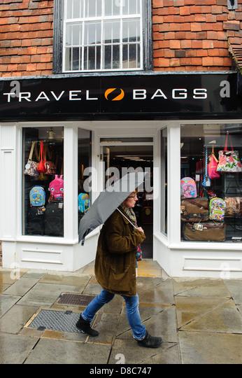 Shopper walking passed a travel bag shop in rain with umbrella up - Stock-Bilder
