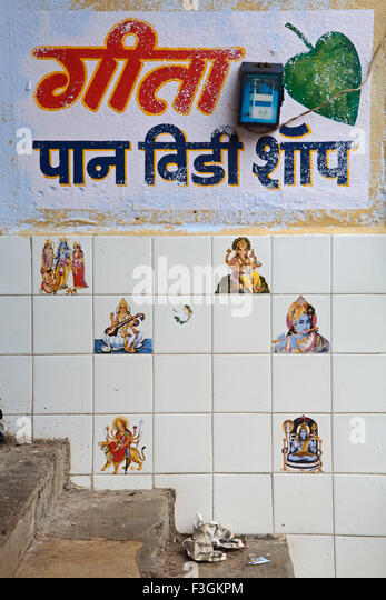 Images of Gods and Goddesses painted on ceramic tiles on the wall near a 'paan' shop discouraging customers - Stock Image