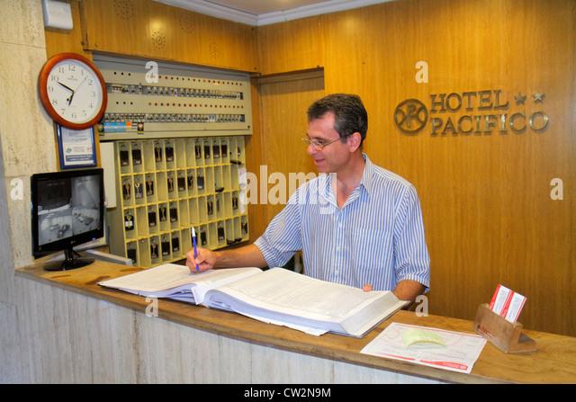 Mendoza Argentina Avenida San Juan Hispanic Hotel Pacifico business lodging front desk Hispanic man clerk job check - Stock Image