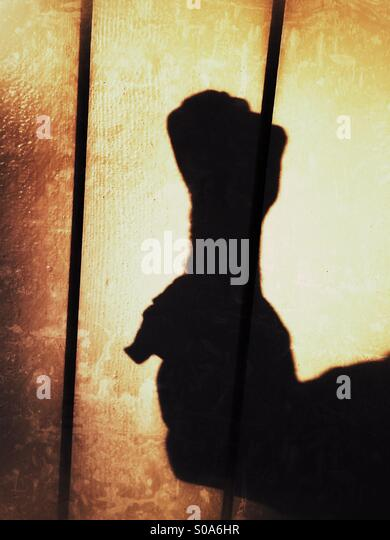 A man casting a shadow on a wall, counting on his hand. Number zero. - Stock Image