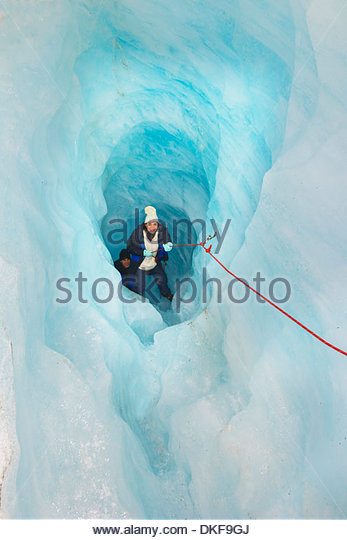 Rock climbers moving up ice cave Fox Glacier, South Island, New Zealand - Stock Image