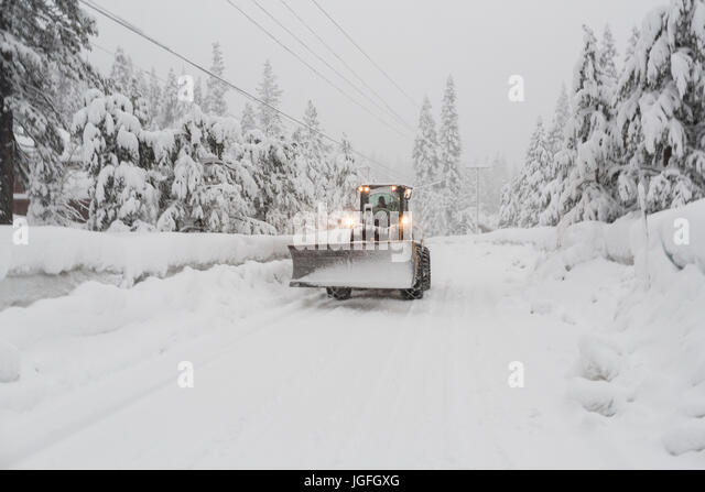 Tractor with snow plow driving on remote road - Stock Image