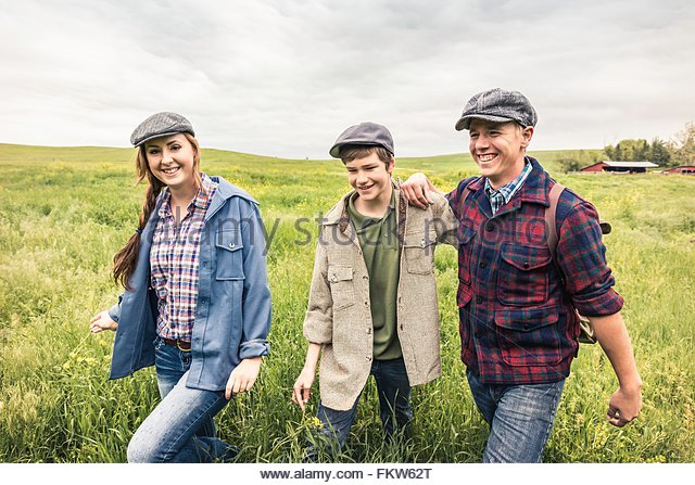 Young adults and teen boy wearing flat caps walking in tall grass looking at camera smiling - Stock Image