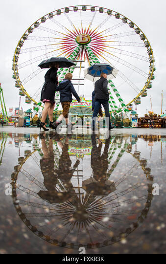 Stuttgart, Germany. 16th Apr, 2016. A family walking past through the rain past the fairy wheel at the 78th Spring - Stock Image
