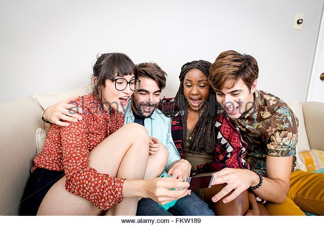Two young hipster couples sitting on apartment sofa laughing at instant photograph - Stock-Bilder