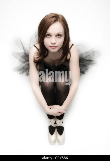 Portrait of teenage dancer sitting on a white background wearing a black tutu. - Stock Image